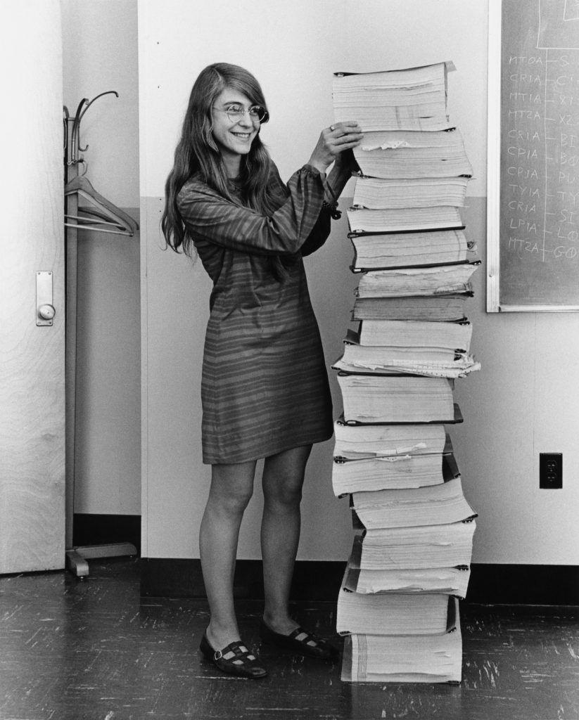 Margaret Hamilton posa junto a los listados de los programas que desarrolló para la navegación de las naves Apolo. Crédito: Wikipedia
